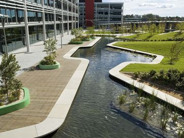 Surrounded by six large floor plate office buildings, the internal courtyard forms the focus for the Optus corporate campus in North Ryde. A 200 metre long ribbon wall unifies the space and articulates the straight podium edge to create a number of sub spaces within the triangular courtyard. Stairs and planted embankments rise up to the ribbon wall to take up the four metre level change between the podium and the courtyard to its south. Storm water detention is handled in two large ponds with an elegant precast edge. Planting is scaled according to the spaces. Tall trees are planted on the embankments and small ornamental tress within the sub spaces at the base of the ribbon wall. The project sought to provide the employees with a variety of richly planted garden spaces in which to gather, socialise and hang out during their breaks. The spatial structure is reinforced by the planting palette. Tall straight trunked spotted gums line the ramps and signify main circulation spaces, whilst small flowering deciduous trees and flowering shrubs define the sub spaces. The ponds are planted with water plants.